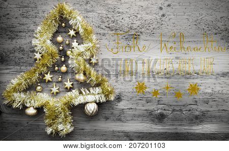 Calligraphy With German Text Frohe Weihnachten Und Ein Gutes Neues Jahr Means Merry Christmas And Happy New Year. Golden Tinsel Christmas Tree. Christmas Ball Ornament On Gray Wooden Background