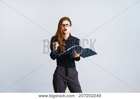 indignant red-haired girl with glasses is holding a ruler and folders with documents in her hands and looking into the camera