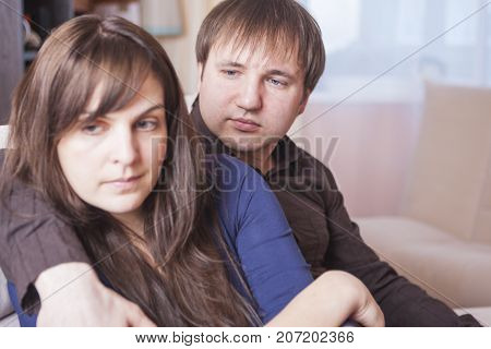 Young Caucasian Couple Trying to solve Relationships Problems. Sitting Together Embraced But With Down Feelings. Horizontal Image Composition