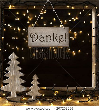 Sign With German Text Danke Means Thank You. Window Frame With Lights In The Night In Background. Christmas Decoration Like Christmas Tree And Fairy Lights.