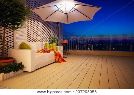 beautiful modern rooftop patio terrace with evening city view