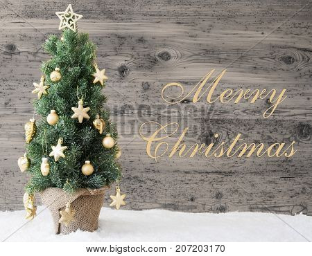 English Text Merry Christmas. Golden Decorated Christmas Tree With Gray Vintage Background. Rustic Wooden Style With Snow