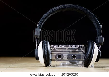 Cassette Tape And Headphones For Listening To Music. Old Good Music From The 80S. Wooden Table.