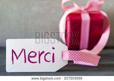 Label With French Text Merci Means Thank You. Pink Gift Or Present With Gray Cement Background