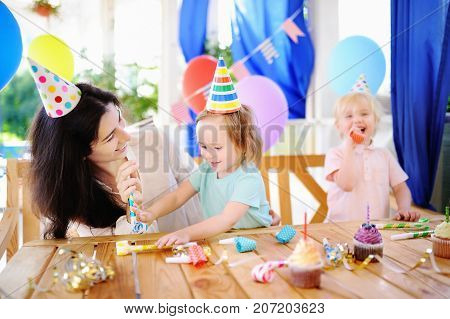 Little Child And Their Mother Celebrate Birthday Party With Colorful Decoration And Cakes With Color