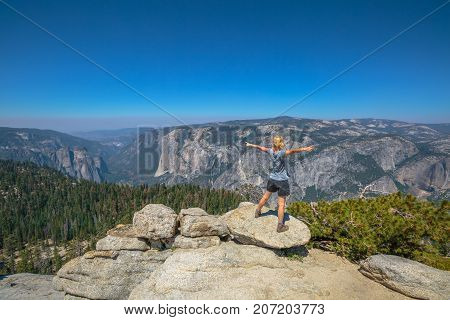Yosemite summit panorama view for a woman after hiking in Yosemite National Park at Sentinel Dome. Aerial view of popular El Capitan from Sentinel Dome. Summer travel in United States, California.
