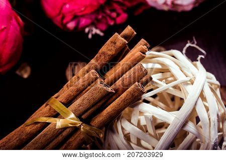 Ground cinnamon, cinnamon sticks, connected with a tray with a bow on a color background in a rustic style. Macro photo with selective focus. Close up food concept. Vintage toning. Retro style.