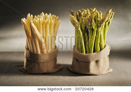 White and green asparagus in cloth bags on canvas background.