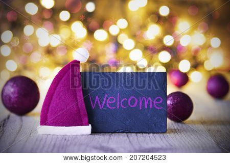 Plate With English Text Welcome. Purple Christmas Ball Ornaments And Santa Claus Hat. Wooden Background With Lights