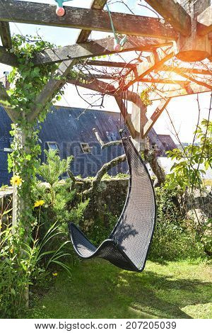 Wicker hanging chair in the garden with green nature background and sun