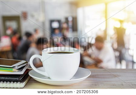 Cup of coffee and notebook smart phone on wooden table with morning sunlight and blur workplace image of abstract bokeh background.