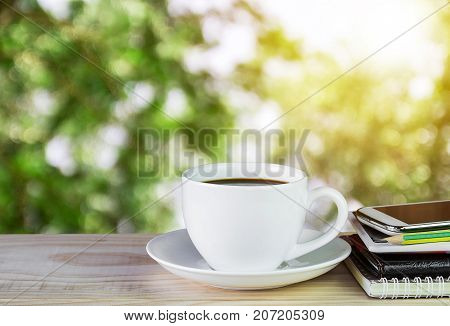 Cup of coffee and notebook smart phone on wooden table with morning sunlight and blur image of abstract bokeh of green color background.