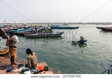 VARANASI INDIA - MARCH 14 2016: Horizontal picture of Japanese man swimming with a whale pool float at Dashashwamedh Ghat in Ganges River during day time in Varanasi India.