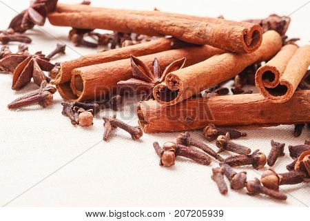 Spices for christmas cakes cinnamon sticks anise stars and cloves on burlap background