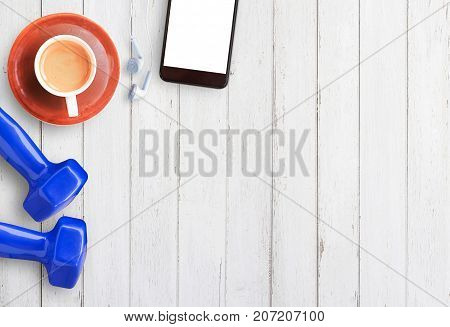 Top view of cup of coffeesmartphone and blue dumbbell on white wooden table background with copy space for any design. Healthy eating dieting slimming and weight loss concept.