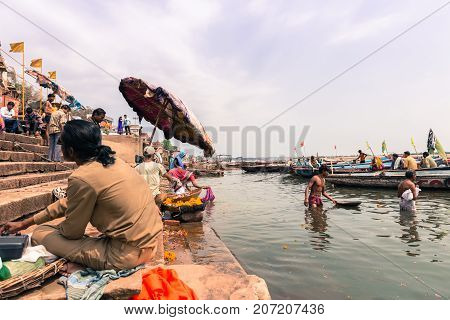 VARANASI INDIA - MARCH 14 2016: Wide angle picture of indian people in daily life at Dashashwamedh Ghat in Ganges River during day time in Varanasi India.