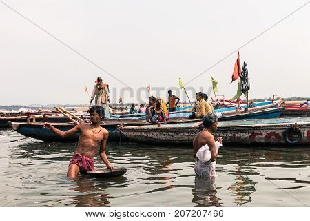 VARANASI INDIA - MARCH 14 2016: Horizontal picture of indian people praying in the holy water of Ganges River during day time in Varanasi India.