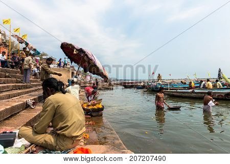 VARANASI INDIA - MARCH 14 2016: Horizontal picture of indian people in daily life at Dashashwamedh Ghat in Ganges River during day time in Varanasi India.