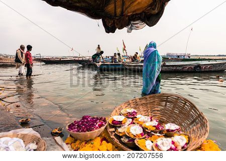 VARANASI INDIA - MARCH 14 2016: Horizontal picture of indian woman in her traditional clothe in the holy water of Ganges River during day time in Varanasi India.