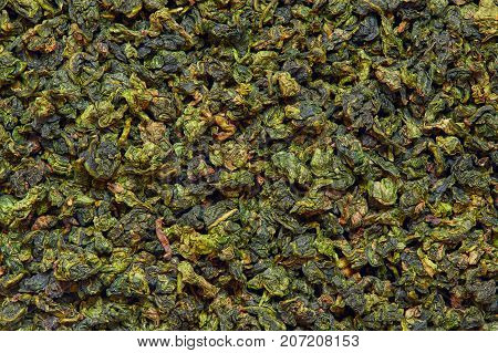 Background texture of dry green Tie Guan Yin Oolong tea leaves