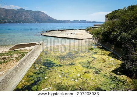 The ditch water full of conferva at the abandoned Yugoslavian military resort in Kupari Croatia.