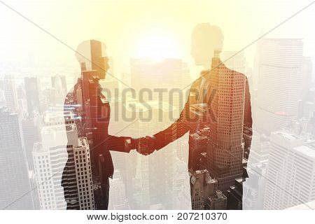 Handshake of two businessperson in a modern office. concept of partnership and teamwork. double exposure