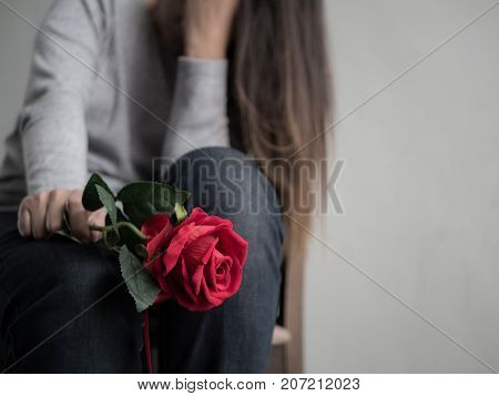 Sad woman sitting and crying with red rose in her hand. Lonly love emotion concept.
