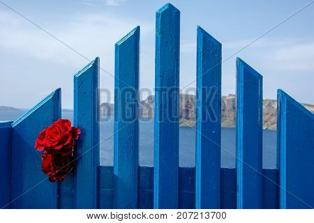 A traditional symmetric door yard with a pair of red roses, Santorini. Honeymoon summer aegean cycladic background.