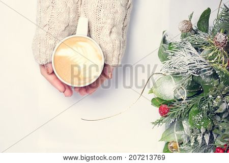 Girl holding cup of coffee with latte art. Christmas background. Hygge and leasure time concept. Pastel colors warm toning. Horizontal