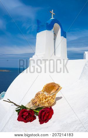 Bell tower of an orthodox church at Santorini with a pair of red roses, Greece. Honeymoon summer aegean cycladic background.