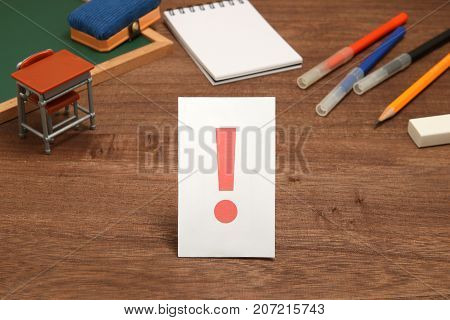 Exclamation mark on white paper with the study tool as the background. Concept of learning inspiration.