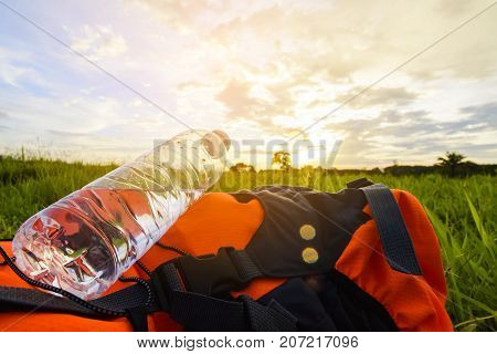 Water bottle on orange backpack on green grass with nature view.