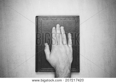 mans hand on the book the oath on the Bible. top view closeup. black and white photo