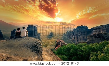 Couple enjoy the breathtaking view of Meteora Roussanou Monastery at sunset, Greece. Geological formations of big rocks with Monasteries  on top of them, on July 20, 2017.