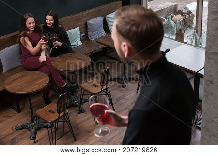 Female seduction. Gossips about male. Flirty women in bar in focus on background, unrecognizable man with wine, flirtation concept