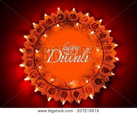 Happy Diwali greeting card design using Beautiful Clay diya lamps lit on diwali night Celebration.  Indian Hindu Light Festival called Diwali, a festival of light