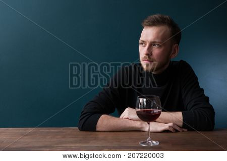 Depressed young man in bar. Sad thoughtful male on blue background with free space, melancholic mood with red wine. Troubles in life, unlucky date