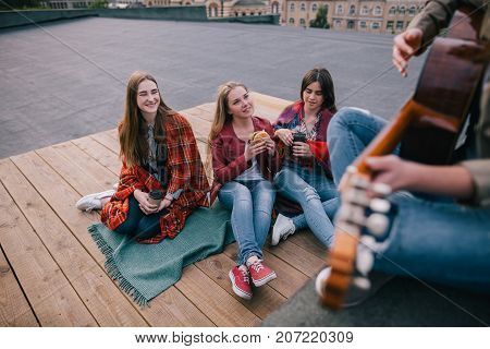 Fans on live music show. Friends leisure. Girls with fast food in hands listen singer's acoustic guitar improvisation.