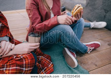 Burger and coffee in hands of young women. Favorite junk food close up. Unhealthy meals and hurry eating, friendship and sharing time together concept