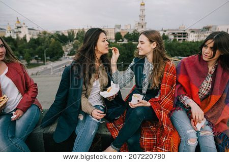 Joyful young girls spending good time together. Close friends sharing french fries in cafe on roof. Unusual places for rest and entertainment, leisure with cheerful atmosphere concept