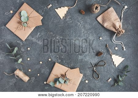 Christmas composition. Christmas gifts and eucalyptus branches on black background. Flat lay top view copy space