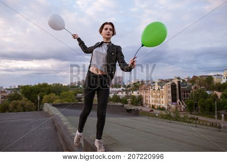 Thoughtful young woman with two toy balloons walking on roof. Dreamy and infantile personality on city background, airiness and hope, fly to dreams and rich imagination concept, free space