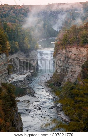 Inspiration Point in early Autumn at dusk is the sight of beautiful Waterfalls and train trestle at Letchworth State Park, NY, portrait