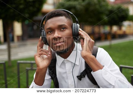 Portrait of african man resting outdoors, listening music in big headphones, and holding it, looking up. Student relaxing, dreaming. Traveler with bag on back enjoying of music.