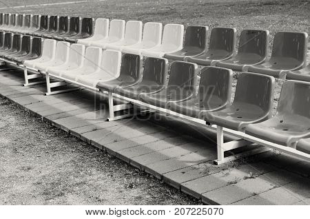 Multicolored benches for sports fans standing in two rows. B.W.