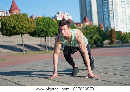 Fit Macho In Tracksuit And Running Shoes On Urban Landscape