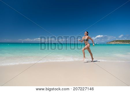 Girl in sexy swimsuit running on beach with white sand turquoise sea or ocean and blue sky on sunny day on natural environment. Sun tanning bathing. Summer vacation. Rest relaxing active leisure