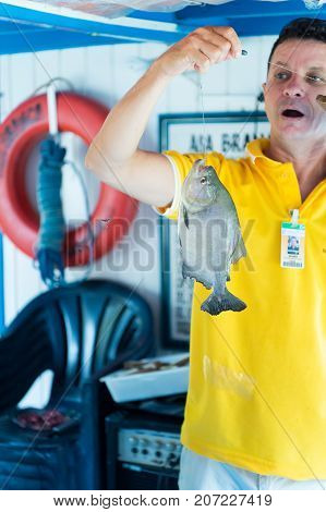 Santarem Brazil - December 02 2015: excited man in yellow tshirt holding fish on line. Fishing activity concept. Active lifestyle and hobby