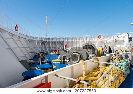 Ship stern deck with nautical ropes mooring winch hook and lifebuoy on sunny blue sky background in Philipsburg Sint Maarten. Sea voyage and travelling. Yachting and boating concept