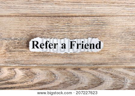 REFER A FRIEND text on paper. Word REFER A FRIEND on torn paper. Concept Image.